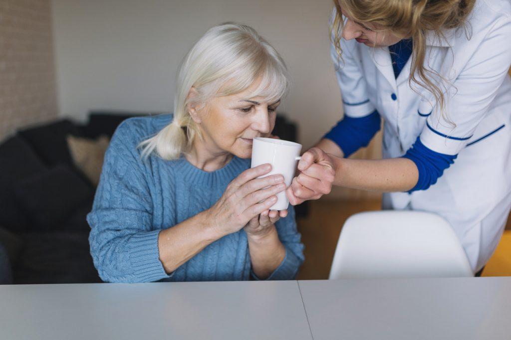 kobieta podaje seniorowi herbatę