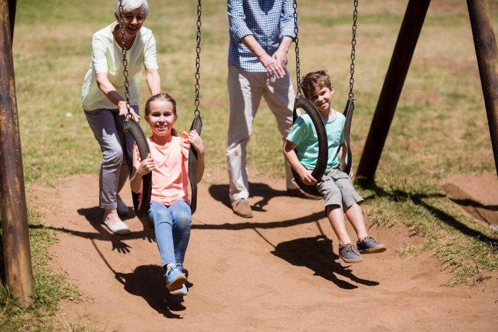 dziadkowie z dziećmi na placu zabaw
