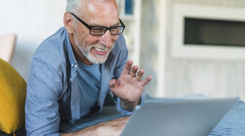 wesoły senior rozmawiający on-line