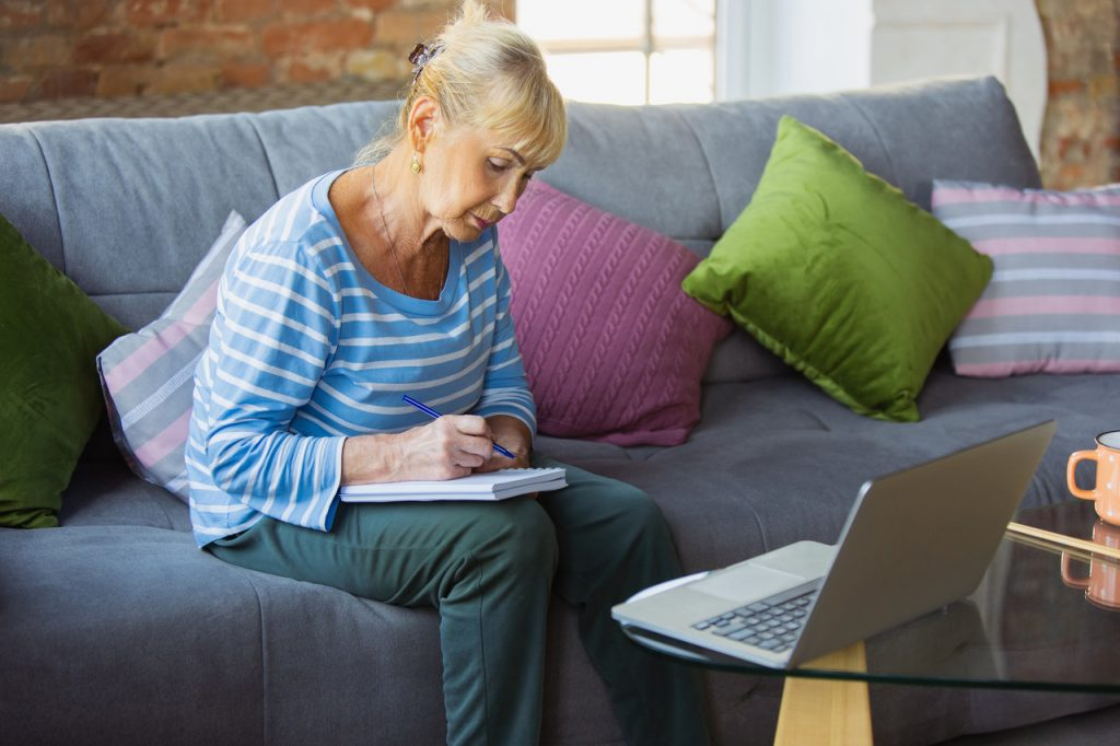starsza kobiera płaci rachunki przez internet